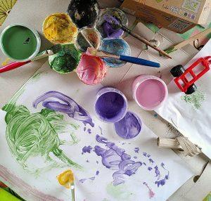 Man sieht ein mit Fingerfarben von Neogrün gemaltes Bild. Auf dem Tisch stehen vier Farbeimer mit grün, gelb, lila und rosa von Neogrün
