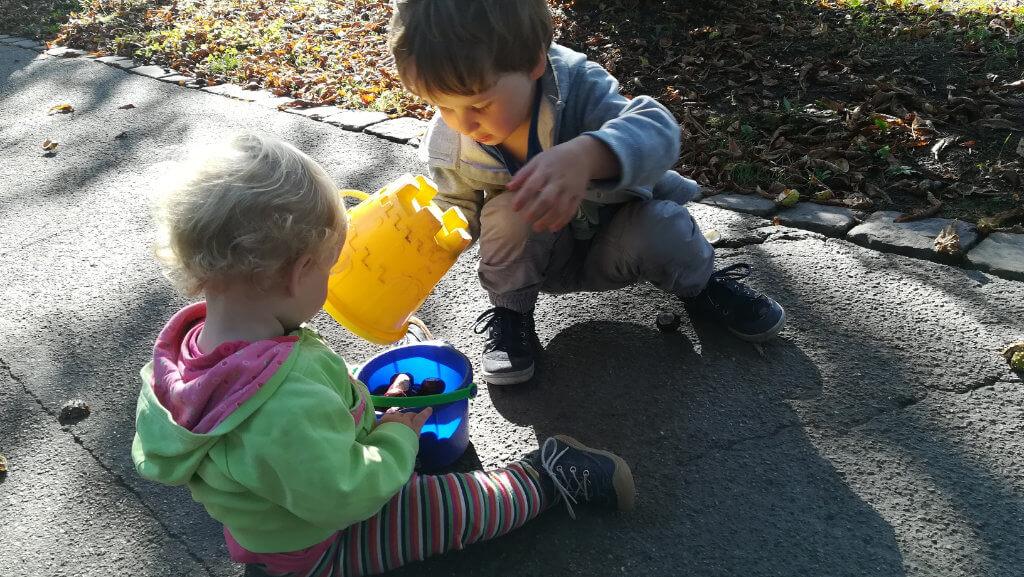Geschenkidee für 2-jährigen Jungen. Man sieht einen Jungen und Mädchen draußen mit Steinen und Eimern spielen.