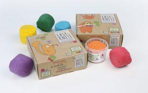 Geschenkidee für zweijährige Jungs. Man sieht Knete in kleinen Eimern in den Farben Lila, Gelb, Grün, Blau, Orange und Rot. Hersteller: neogrün