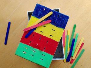 Geschenkidee für zweijährige Jungs. DIY Farbsortierspiel aus einem Karton und farbigen Holzstäbchen.