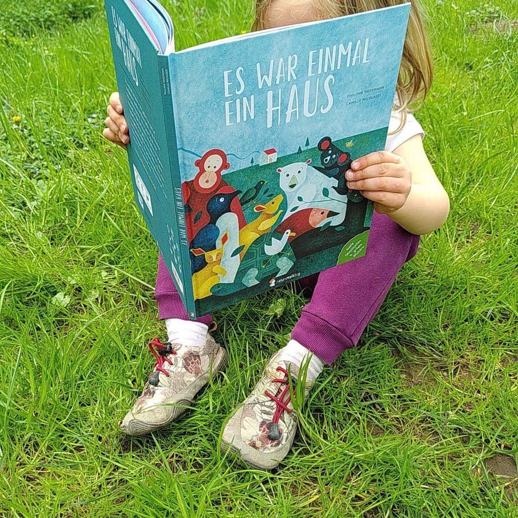 Kind sitzt mit Bilderbuch auf Wiese